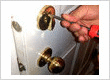 A locksmith technician repairs a deadbolt lock