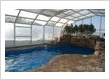 Attached Operable Single Peak pool enclosure 43 ft wide x 24 ft long with 2 bays, both operable, moving toward the house coming to rest over the roof of the house, includes automatic electric drive sy