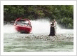 A Shotover Jet jetboat zooms pas a bride and groom on the shores of the Shotover River, Queenstown